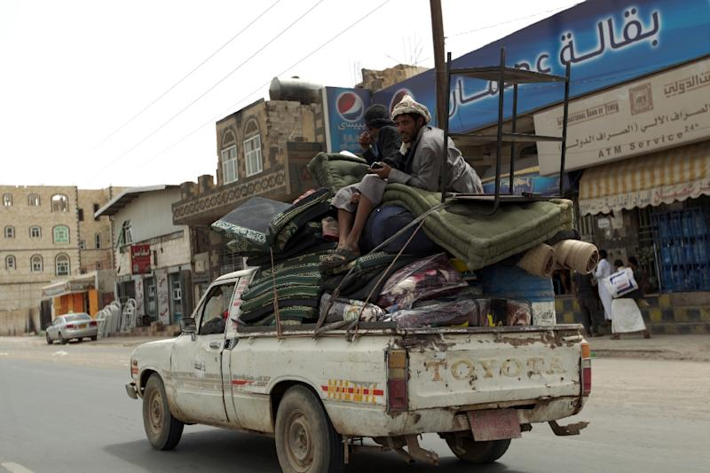 Yemenis ride a pick-up truck loaded with personal belongings as they flee from the international airport neighborhood in the capital Sanaa on April 6, 2015