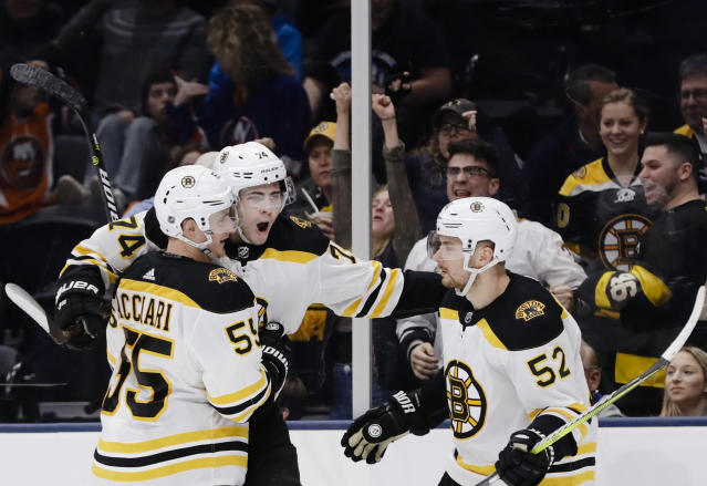 Boston Bruins' Jake DeBrusk, center, celebrates with teammates Noel Acciari (55) and Sean Kuraly (52) after scoring a goal during the third period of an NHL hockey game against the New York Islanders Tuesday, March 19, 2019, in Uniondale, N.Y. The Bruins won 5-0. (AP Photo/Frank Franklin II)