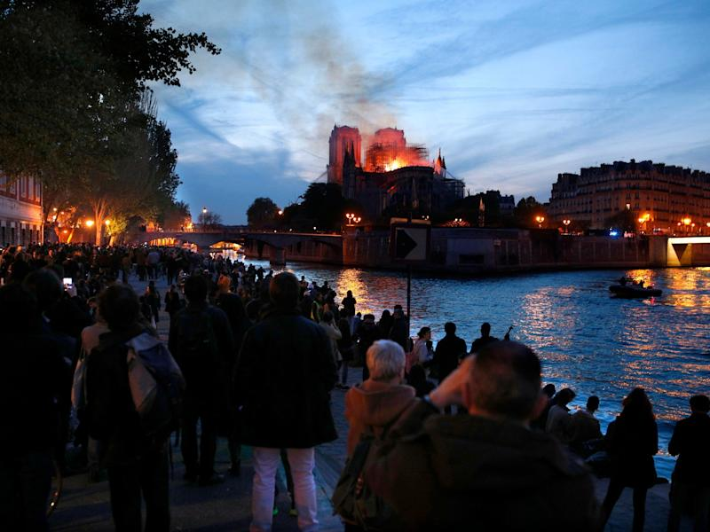 Notre Dame cathedral fire: Parisians lining Seine watch in disbelief as city's beloved landmark is ravaged - 'It was a symbol of France'