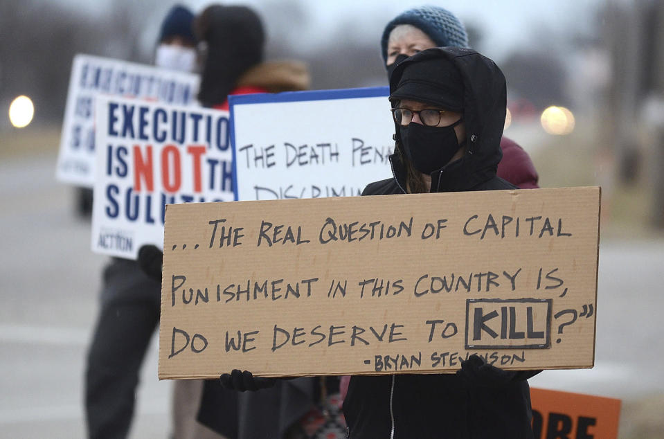 Christina Bollo of Urbana, Illinois, holds a sign as she protests the execution of Corey Johnson, near the Federal Correctional Complex, Thursday, Jan. 14, 2021, in Terre Haute, Ind. (Joseph C. Garza/The Tribune-Star via AP)