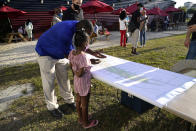 Darrick Rudolph shows his daughter Aliyah plans for a proposed Underdeck park at a community meeting, Wednesday, April 14, 2021, in the Overtown neighborhood in Miami. The park is part of an infrastructure project involving the new Signature Bridge being built over the neighborhood. (AP Photo/Lynne Sladky)