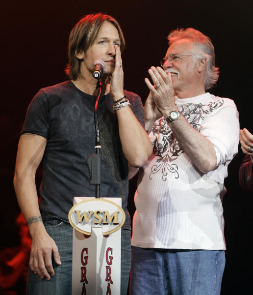 Keith Urban, left, is applauded by Joe Bonsall of The Oak Ridge Boys after it was announced that Urban has been selected to become a member of the Grand Old Opry during the All for the Hall concert on Tuesday, April 10, 2012, in Nashville, Tenn. The concert is a benefit for the Country Music Hall of Fame and Museum. (AP Photo/Mark Humphrey)