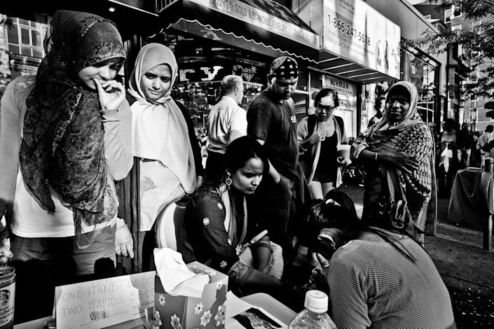 <p>Crowded 74th Street henna stands, night before the Muslim holiday Eid in Jackson Heights, Queens, N.Y., in September 2015. (Photo: Yunghi Kim/Contact Press Images) </p>