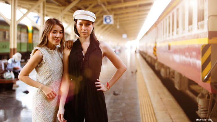 Lesbian Asian couple, one of whom is a trans woman, on train platform