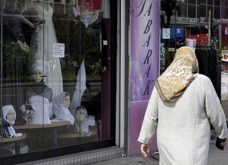 A woman wearing a headscarf walks through a street in Berlin's Neukoelln district
