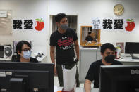 Staff members design their layout for the last edition of the newspaper at the Apple Daily headquarters in Hong Kong, Wednesday, June 23, 2021. Hong Kong's pro-democracy Apple Daily newspaper will stop publishing Thursday, following last week's arrest of five editors and executives and the freezing of $2.3 million in assets under the city's year-old national security law. (AP Photo/Kin Cheung)