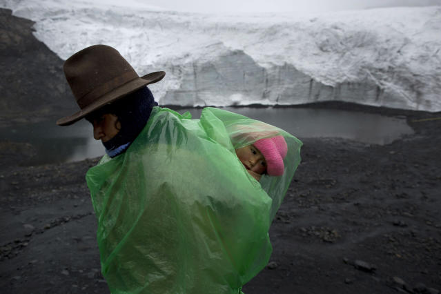<p>Fausta Ortiz, 38, stands guard over the Pastoruri glacier while carrying her daughter Lisoyun, 2, in Huaraz, Peru, Dec. 4, 2014. According to Alejo Cochachin, coordinator of the glaciology unit, the Pastoruri glacier retreated 576 meters between 1980 and 2014. Peru's glaciers have lost more one-fifth of their mass in just three decades, and 70 percent of the 30 million people in Peru who inhabit the Pacific coastal desert depend on glacial runoff for hydropower and to irrigate crops. This means their electricity and long-term food security could also be at risk. Higher alpine temperatures are killing off plant and animal species in cloud forests, and scientists predict Pacific fisheries will suffer. (Photo: Rodrigo Abd/AP) </p>