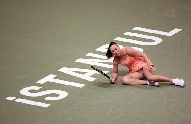 Jelena Jankovic of Serbia falls as she returns a shot to Li Na of China during their tennis match at the WTA championship in Istanbul, Turkey, Thursday, Oct. 24, 2013. The world's top female tennis players compete in the championships which runs from Oct. 22 until Oct. 27.(AP Photo)
