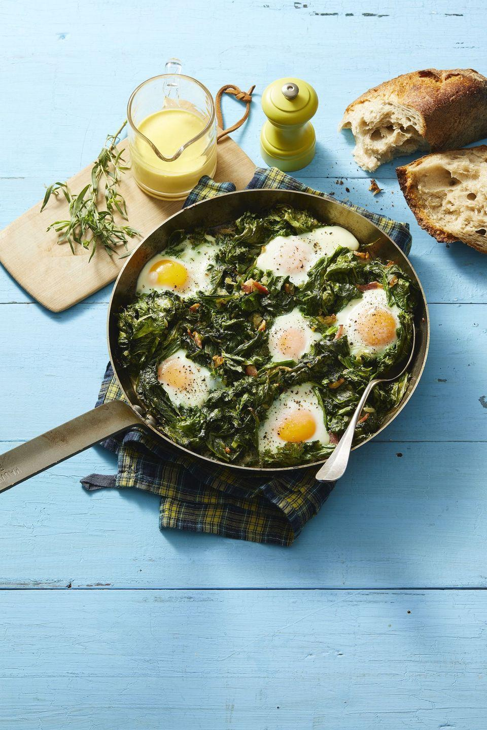 """<p>Part Eggs Benedict, part Shakshuka this is the perfect vegetarian dish to serve for breakfast, brunch, or dinner. </p><p><em><a href=""""https://www.womansday.com/food-recipes/a32320198/skillet-eggs-with-mustard-greens-and-hollandaise-recipe/"""" rel=""""nofollow noopener"""" target=""""_blank"""" data-ylk=""""slk:Get the Skillet Eggs With Mustard Greens and Hollandaise recipe."""" class=""""link rapid-noclick-resp"""">Get the Skillet Eggs With Mustard Greens and Hollandaise recipe. </a></em></p>"""