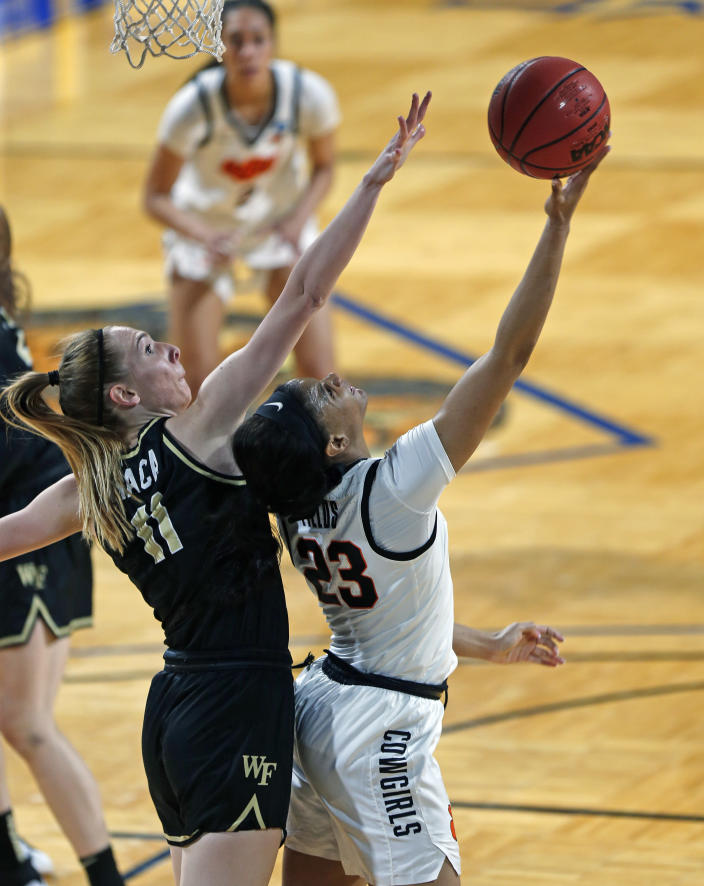 Oklahoma State guard Lauren Fields (23) shoots a reverse lay-up over Wake Forest forward Ivana Raca (11) during the first half of a college basketball game in the first round of the women's NCAA tournament at the Greehey Arena in San Antonio, Texas, Sunday, March 21, 2021. (AP Photo/Ronald Cortes)