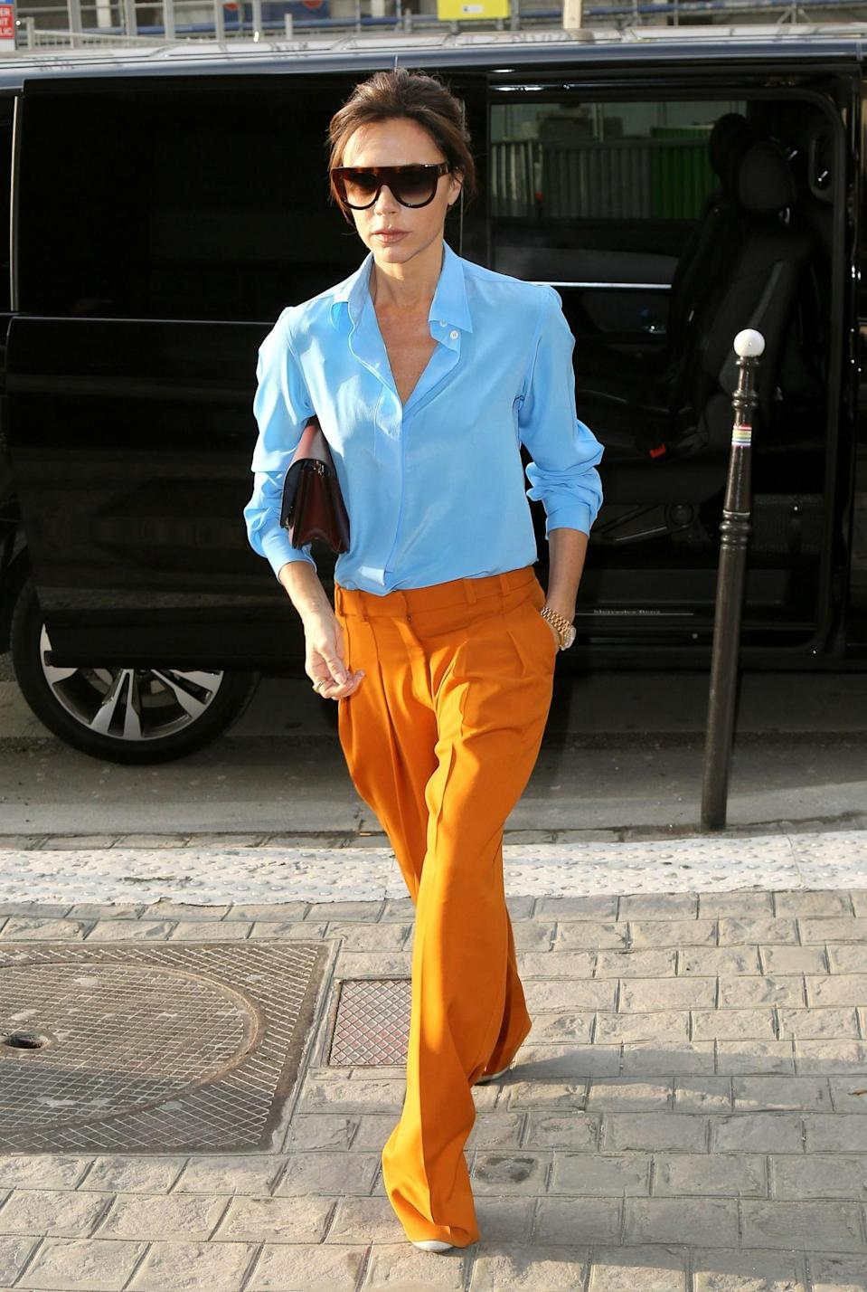 <p>In Paris, VB worked a two-tone eye-catching look, comprising of burnt orange trousers and a sky blue blouse – both from her own collection. <em>[Photo: Getty]</em> </p>
