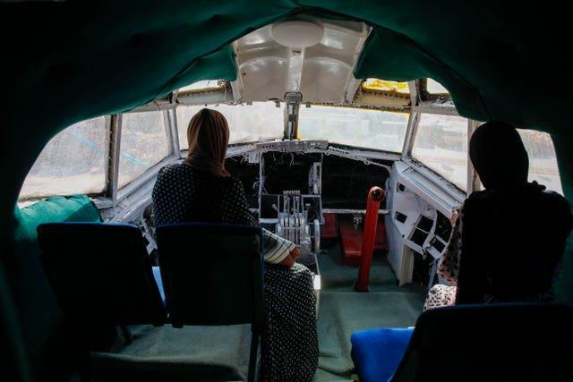Palestinians visit the cockpit of a Boeing 707 after the plane was converted to a cafe restaurant, in Wadi Al-Badhan, near the West Bank city of Nablus