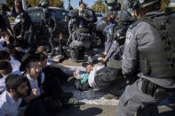 Israeli police officers clash with ultra-Orthodox Jews during a protest over the coronavirus lockdown restrictions, in Ashdod, Israel, Sunday, Jan. 24, 2021. As he seeks re-election, Prime Minister Benjamin Netanyahu has turned to a straightforward strategy: Count on the rock-solid support of his ultra-Orthodox political allies and stamp out the coronavirus pandemic with one of the world's most aggressive vaccination campaigns. But with ultra-Orthodox communities openly flouting safety guidelines and violently clashing with police trying to enforce them, this marriage of convenience is turning into a burden. (AP Photo/Oded Balilty)