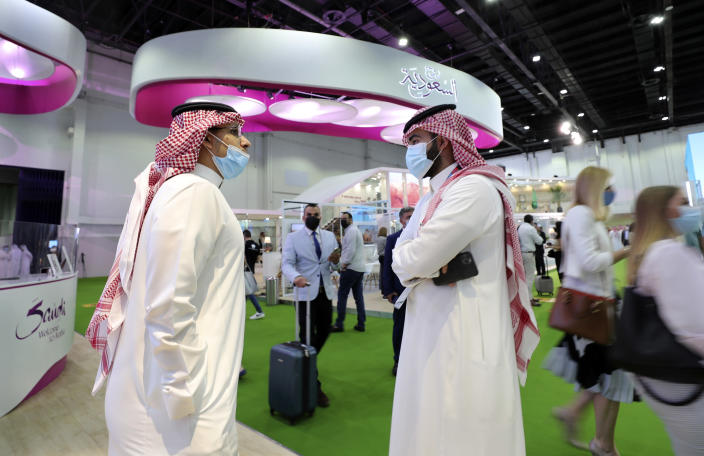 Saudi exhibitors talk at their stand at the Arabian Travel Market exhibition, in Dubai, United Arab Emirates, Sunday, May 16, 2021. Vaccinated Saudis are allowed to leave the kingdom for the first time in more than a year on Monday as the country eases a ban on international travel aimed at containing the spread of the coronavirus and its new variants. (AP Photo/Kamran Jebreili)