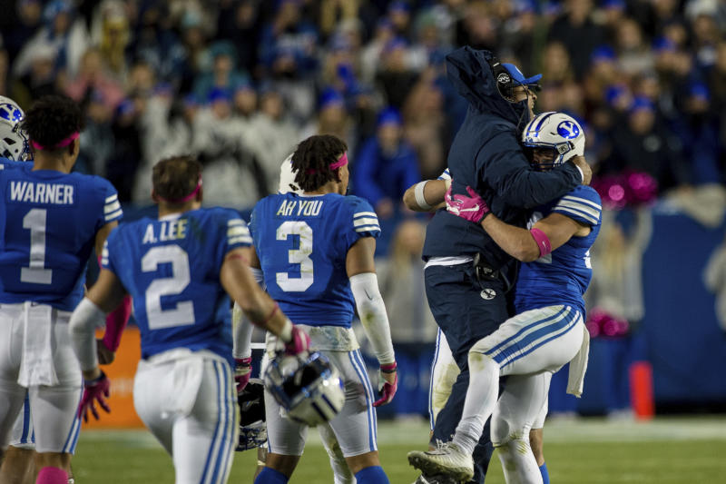 BYU head coach Kalani Sitake jumps into the arms of defensive back Austin Kafentzis, right, during the second half against Boise State in an NCAA football game Saturday, Oct. 19, 2019, in Provo, Utah. (AP Photo/Tyler Tate)