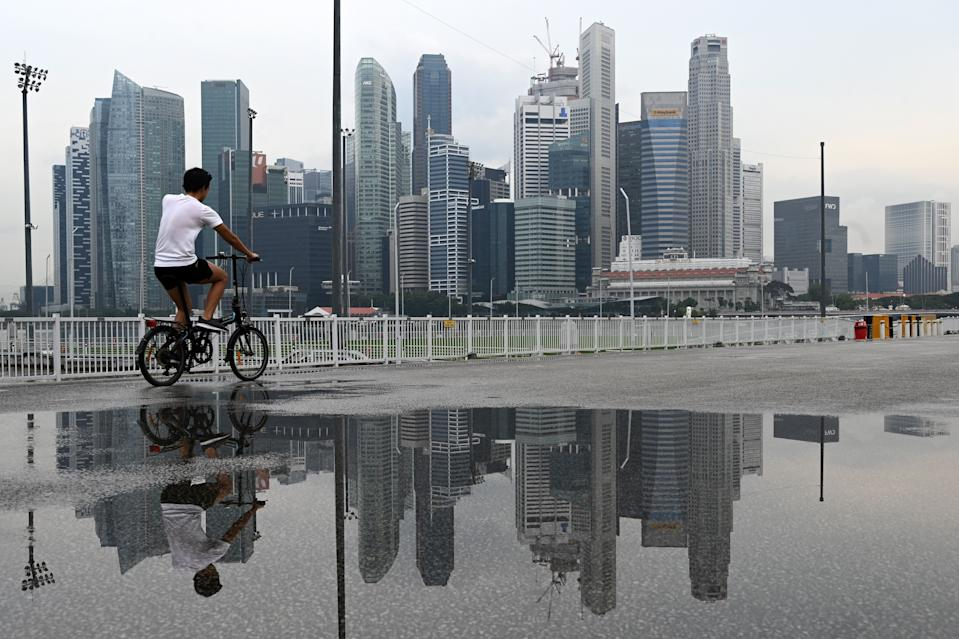 A cyclist rides before the city skyline at Marina bay in Singapore. (Photo by ROSLAN RAHMAN / AFP) (PHOTO: Rosland Rahman/AFP via Getty Images)