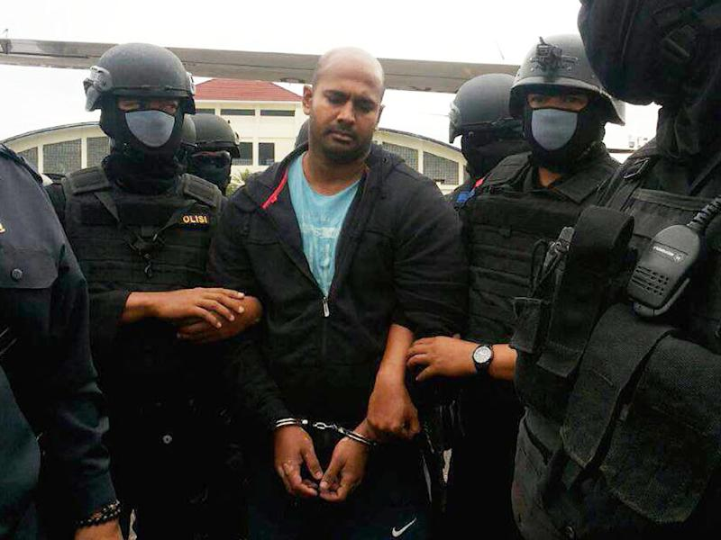 Police commandos escort Australian drug smuggler Myuran Sukumaran as he arrives in Cilacap in central Java island on March 4, 2015 on his way to a maximum security prison in Nusakambangan island (AFP Photo/)