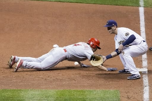 Cincinnati Reds' Shogo Akiyama slides safely back to first with Milwaukee Brewers' Logan Morrison covering on a pick off attempt during the ninth inning of a baseball game Saturday, Aug. 8, 2020, in Milwaukee. (AP Photo/Morry Gash)