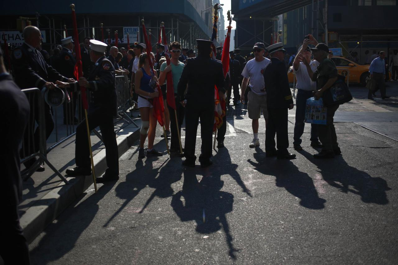 Members of the New York City Fire Department and others stand with flags after a moment of silence honoring the victims of the 9/11 attacks, outside the World Trade Center site in New York September 11, 2013. Bagpipes, bells and a reading of the names of the nearly 3,000 people killed when hijacked jetliners crashed into the World Trade Center, the Pentagon and a Pennsylvania field marked the 12th anniversary of the September 11 attacks in 2001. REUTERS/Shannon Stapleton (UNITED STATES - Tags: ANNIVERSARY POLITICS)