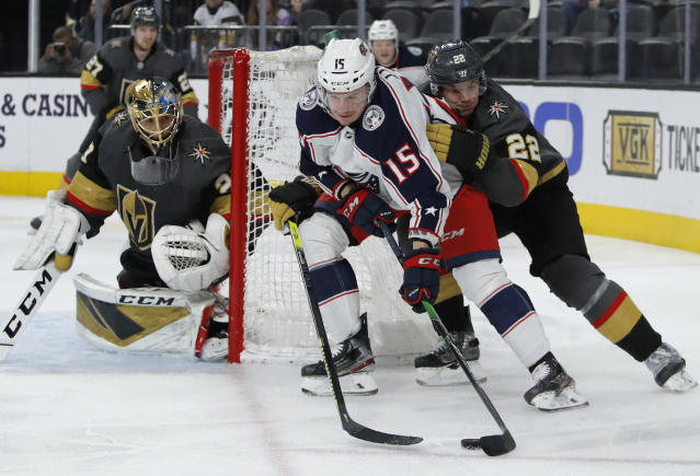 Columbus Blue Jackets left wing Jakob Lilja (15) skates with the puck next to Vegas Golden Knights defenseman Nick Holden (22) during the third period of an NHL hockey game Saturday, Jan. 11, 2020, in Las Vegas. (AP Photo/John Locher)