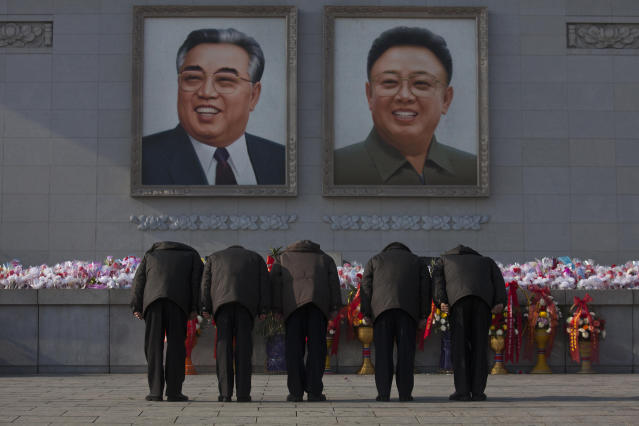 North Koreans bow beneath portraits of the late leaders Kim Jong Il and Kim Il Sung in Pyongyang on Tuesday, Dec. 17, 2013. Across the capital city, North Koreans observed the second anniversary of the death of Kim Jong Il. (AP Photo/David Guttenfelder)