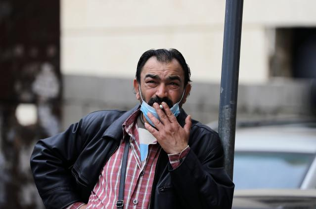 A man is pictured smoking a cigarette after pushing his mask away in Beirut on 12 March. Lebanon has had 248 confirmed cases since the coronavirus outbreak was identified. (Getty Images)