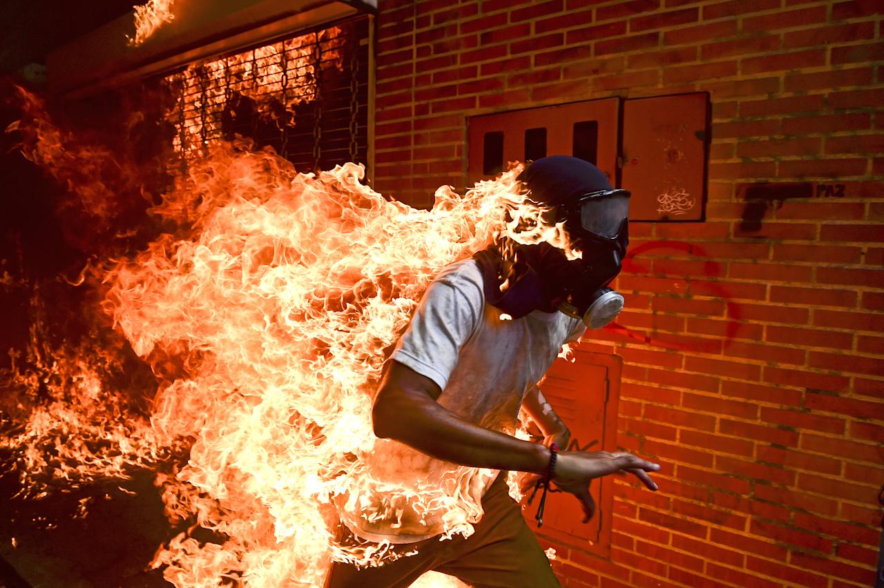 <p>Venezuela crisis: José Víctor Salazar Balza (28) catches fire amid violent clashes with riot police during a protest against President Nicolás Maduro, in Caracas, Venezuela, May 3, 2017.<br />President Maduro had announced plans to revise Venezuela'€™s democratic system by forming a constituent assembly to replace the opposition-led National Assembly, in effect consolidating legislative powers for himself. Opposition leaders called for mass protests to demand early presidential elections. Clashes between protesters and the Venezuelan national guard broke out on 3 May, with protesters (many of whom wore hoods, masks or gas masks) lighting fires and hurling stones. Salazar was set alight when the gas tank of a motorbike exploded. He survived the incident with first- and second-degree burns. (Photo: Ronaldo Schemidt/AFP) </p>
