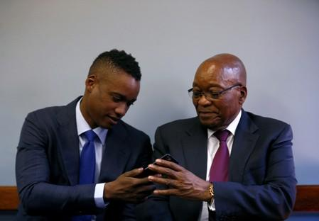 FILE PHOTO: Former South African president Jacob Zuma hands a mobile phone to his son Duduzane ahead of his appearance at the Specialised Commercial Crimes Court in Johannesburg
