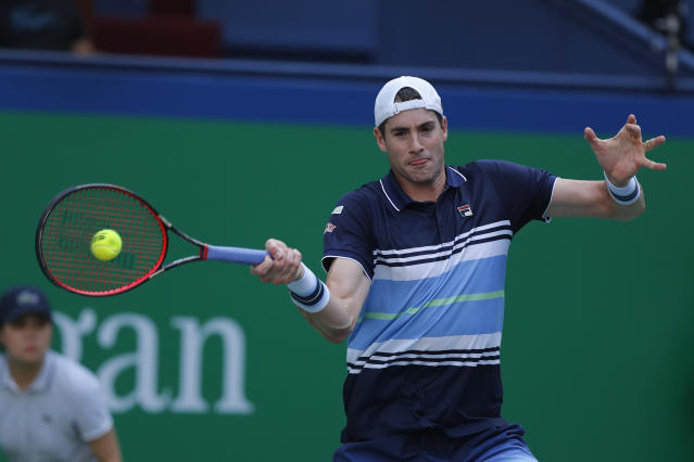 John Isner of the United States hits a return shot against Novak Djokovic of Serbia during the men's singles match at the Shanghai Masters tennis tournament at Qizhong Forest Sports City Tennis Center in Shanghai, China, Thursday, Oct. 10, 2019. (AP Photo/Andy Wong)