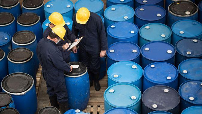 Group of men working at a chemical warehouse classifying barrels.