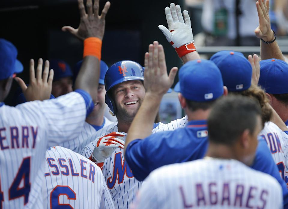 Teammates greet New York Mets' Kirk Nieuwenhuis, center, after he hit a second-inning solo home run that hit the outfield wall and was video-reviewed to confirm the on-field ruling in a baseball game against the Arizona Diamondbacks in New York, Sunday, July 12, 2015. (AP Photo/Kathy Willens)