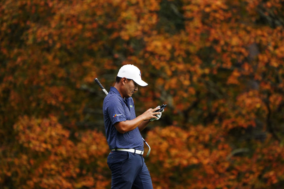 Sung Kang, of South Korea, checks his notes as walks along the second fairway during a practice round for the Masters golf tournament Monday, Nov. 9, 2020, in Augusta, Ga. (AP Photo/Matt Slocum)