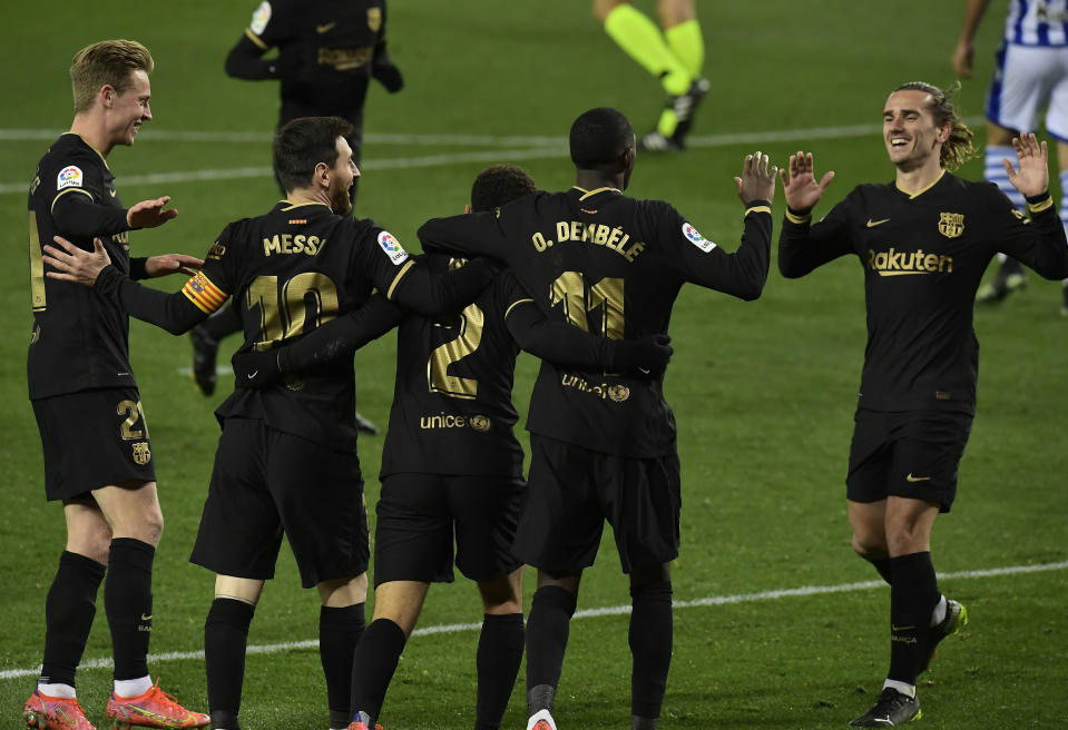 Barcelona's Sergino Dest celebrates with team mates scoring his side's 3rd goal during the Spanish La Liga soccer match between Real Sociedad and FC Barcelona at Reale Arena stadium in San Sebastian, Spain, Sunday, March. 21, 2021. (AP Photo/Alvaro Barrientos)