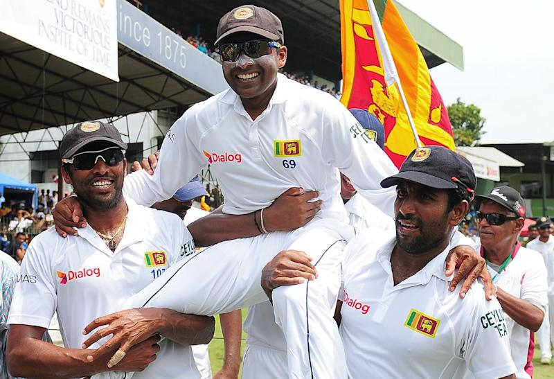Sri Lanka's Mahela Jayawardene (C) smiles as teammates Chanaka Welegedara (L) and Dhammika Prasad (R) carry him around the pitch in a lap of honour at the Sinhalese Sports Club (SSC) Ground in Colombo on August 18, 2014 (AFP Photo/Lakrawuran Wanniarachchi)