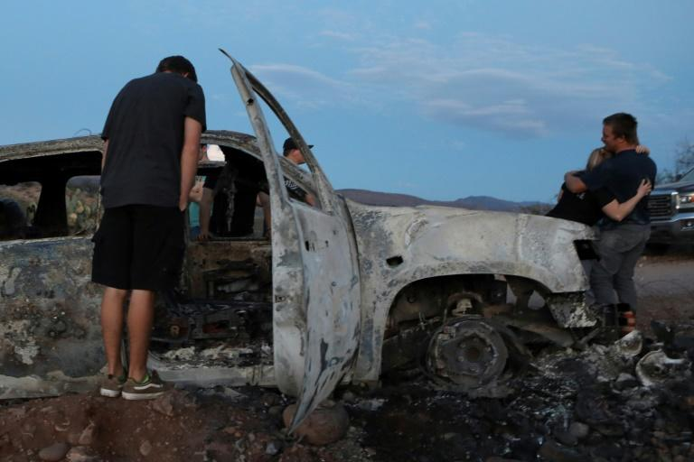 Members of the LeBaron family look at a car that was fired upon and burned during an ambush in Bavispe, Sonora mountains, Mexico, on November 5, 2019 (AFP Photo/HERIKA MARTINEZ)