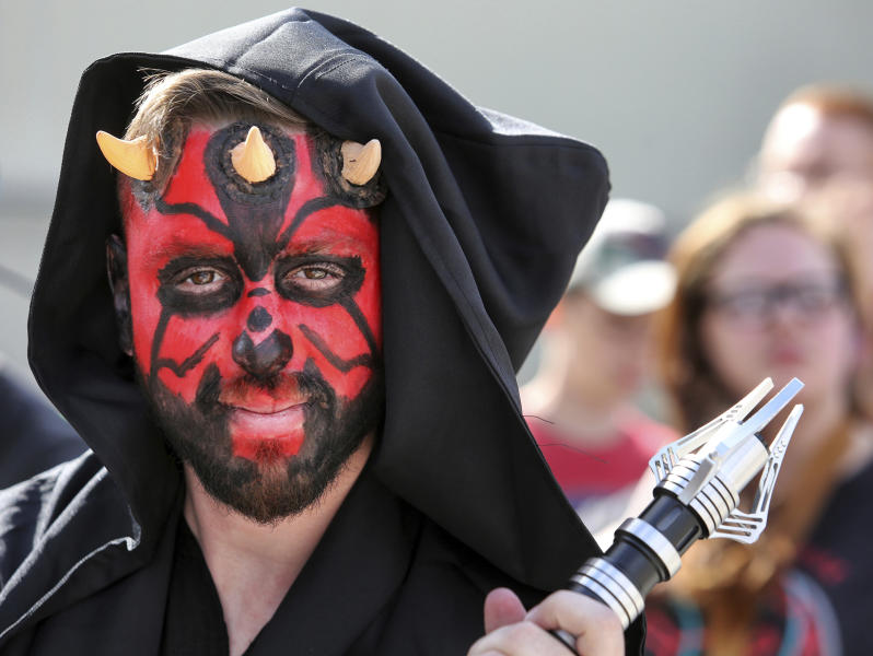 Costumed fans of the Star Wars franchise wait in a massive line outside the Orange County Center, in Orlando, Fla., to attend the 2017 Star Wars Celebration, Thursday, April 13, 2017, marking the 40th anniversary of the original 1977 Star Wars film. Thousands of fans waited for hours in the line, estimated to be more than a mile long. (Joe Burbank/Orlando Sentinel via AP)