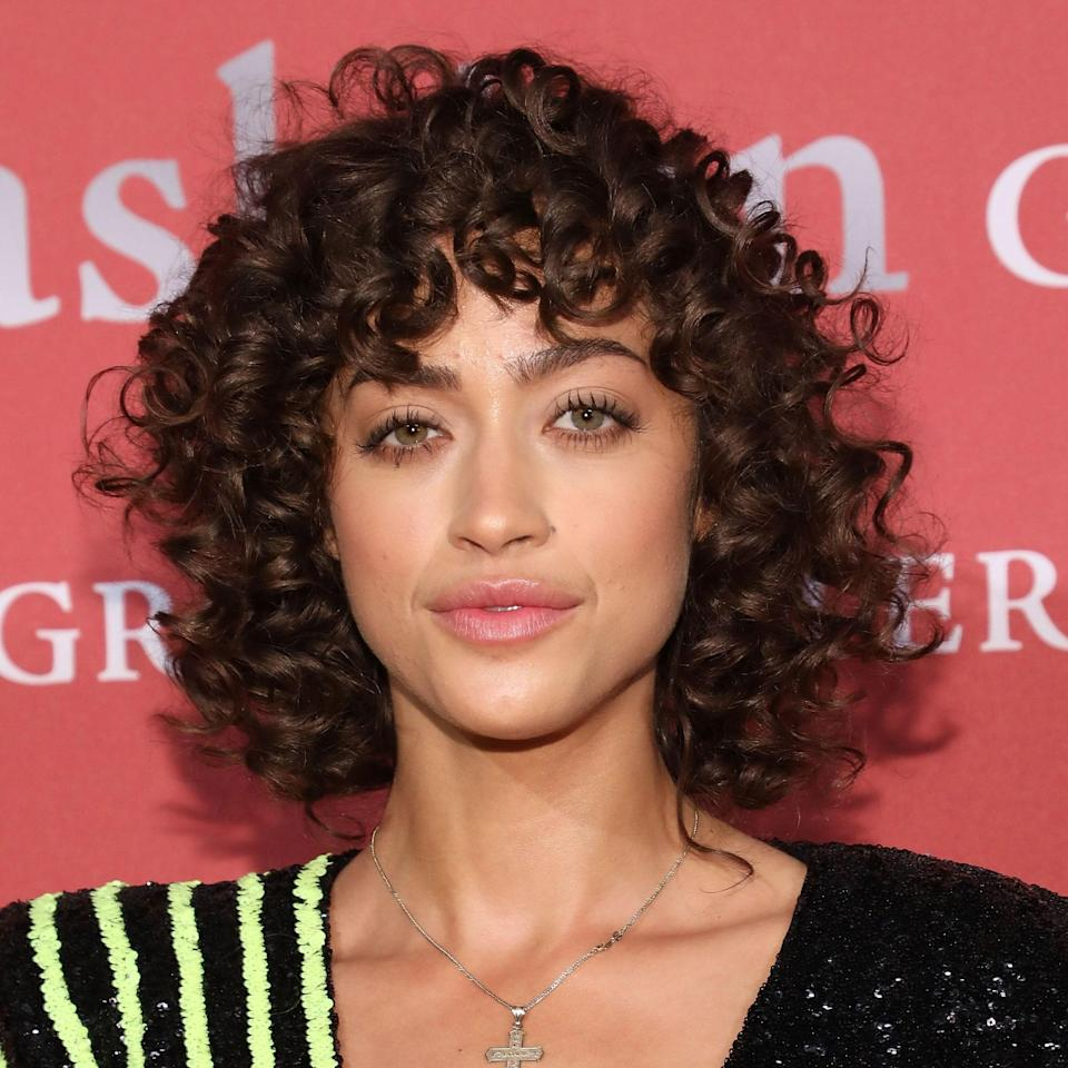 """<p>Alanna Arrington's curly hair looks super light and defined here. """"The blunt cut above the shoulders allows for the curls to fall perfectly around her face,"""" Hardges says of the model. What hair type does this cut work for? """"Wavy to curly textures so you can best see the shape of the cut and the fringe,"""" she says.</p> <p>To style, Hardges notes to """"shingle (define each curl, section by section, using a product of choice) her curls. I would use <a href=""""https://shop-links.co/1744288504219433932"""" rel=""""nofollow noopener"""" target=""""_blank"""" data-ylk=""""slk:Paul Mitchell's Foaming Pomade"""" class=""""link rapid-noclick-resp"""">Paul Mitchell's Foaming Pomade</a>."""" Then, use <a href=""""https://shop-links.co/1744288548818816877"""" rel=""""nofollow noopener"""" target=""""_blank"""" data-ylk=""""slk:single prong clips"""" class=""""link rapid-noclick-resp"""">single prong clips</a> at the scalp to keep the volume as your hair dries naturally.</p>"""