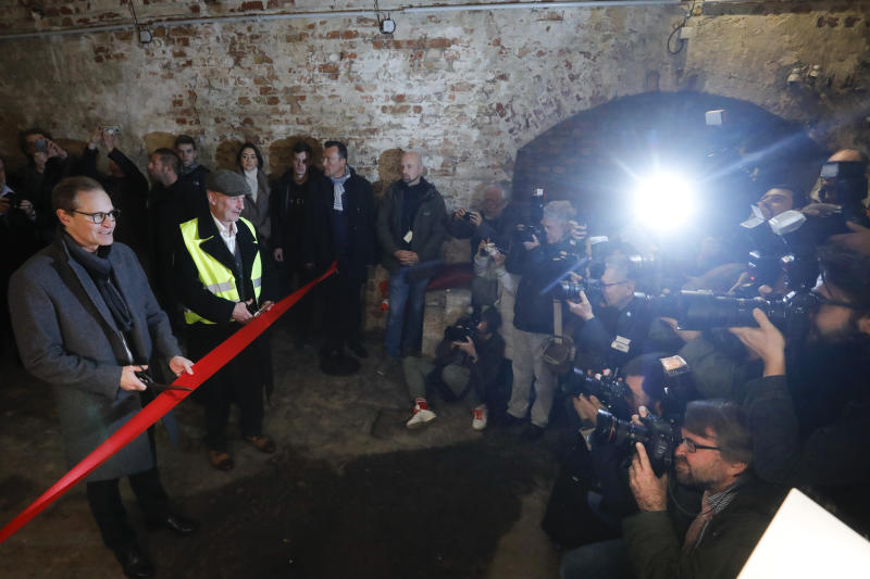 Berlin Mayor Michael Mueller official opens an escape tunnel, underneath the Berlin Wall which divided the city for 28 years during the Cold War, for public for the first time in Berlin, Germany, Thursday, Nov. 7, 2019.The tunnel was built by a group of people who had escaped earlier from communist East Germany to West Berlin. They wanted to help friends and family to flee to the West, too, but days before it was finished, East German officials discovered and destroyed it. (AP Photo/Markus Schreiber)