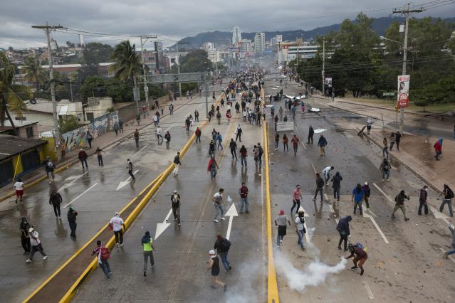 <p>Supporters of Libre Alliance presidential candidate Salvador Nasralla throw rocks at riot police near the National Institute of Professional Training, where election ballots are stored, in Tegucigalpa, Honduras, Thursday, Nov. 30, 2017. (Photo: Rodrigo Abd/AP) </p>