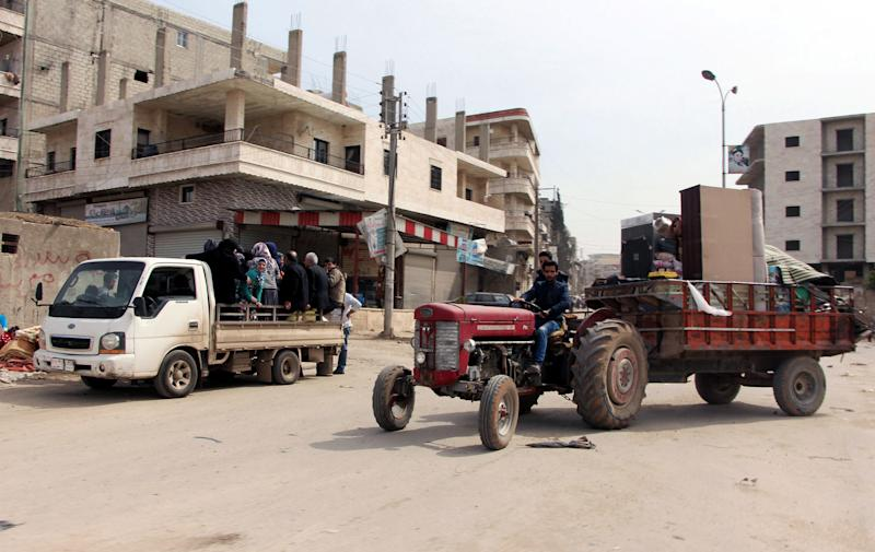 Residents who fled fighting return to the city center of Afrin, northwestern Syria, Monday, March 19, 2018, a day after Turkish troops and allied Free Syrian Army fighters took the control of the area. Turkey's President Recep Tayyip Erdogan said Monday following victory in Syria's Afrin region, his country will expand its military operations into other Kurdish-held areas in Syria as well as in Iraq's Sinjar region.(Hasan Kırmızitaş/DHA-Depo Photos via AP)
