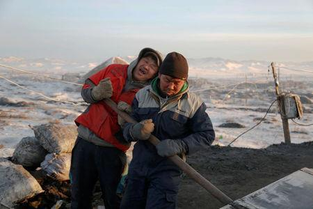 People work at a primitive coal mine outside Ulaanbaatar, Mongolia January 27, 2017. The miners at the Nalaikh coal deposit, outside the Mongolian capital, go as much as 60 meters underground to mine the coal. REUTERS/B. Rentsendorjj