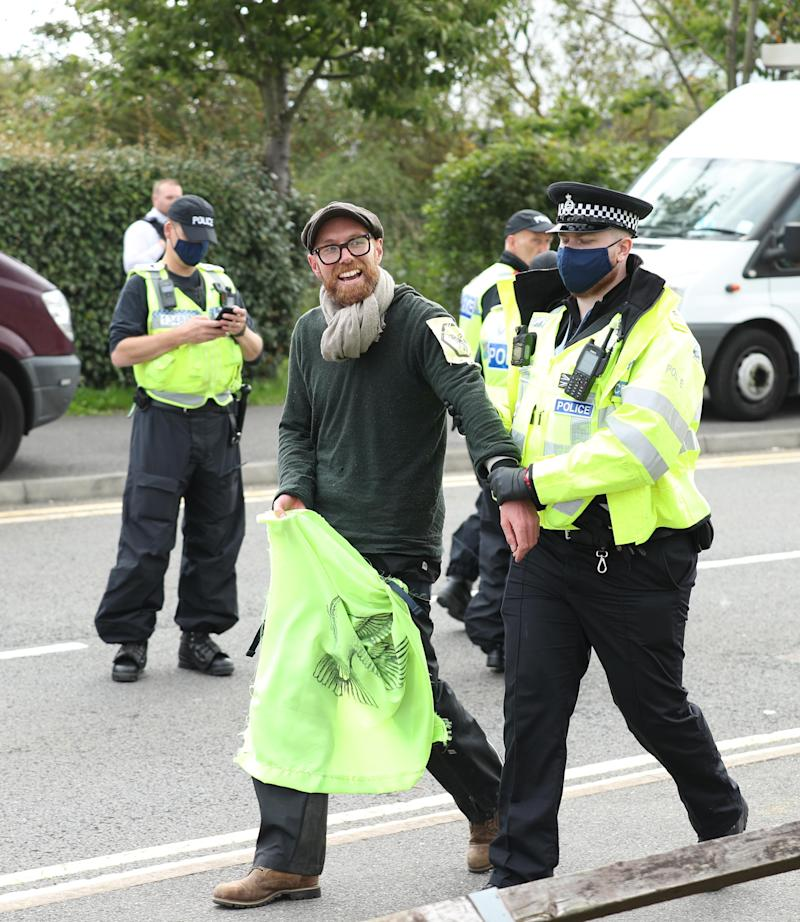 One of the protesters from the bamboo lock-ons is lead away by a police officer at Broxbourne, Hertfordshire.