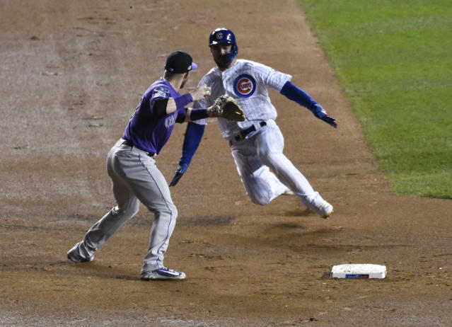 Colorado Rockies shortstop Trevor Story, left, forces out Chicago Cubs' Kris Bryant, right, at second base and throws to first base to complete a double play during the sixth inning of the National League wild-card playoff baseball game, Tuesday, Oct. 2, 2018, in Chicago. (AP Photo/David Banks)