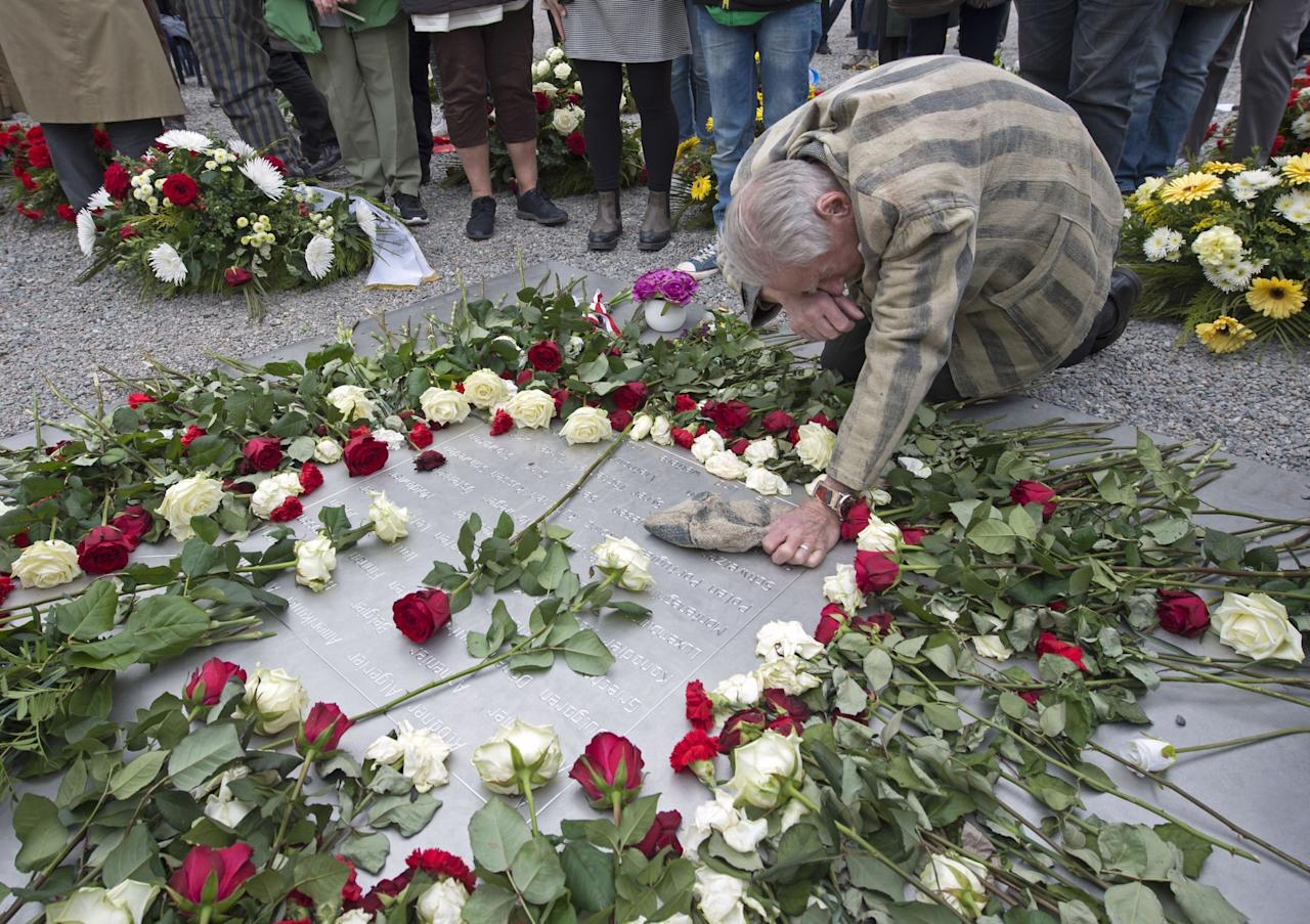 <p>Nazi concentration camp survivor Alexander Bytschok of Kiev, Ukraine, mourns on a metal plaque during the commemoration ceremonies for the 72th anniversary of the liberation of the camp. (Rex features) </p>