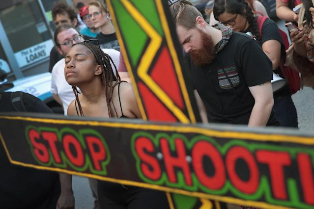 <p>Demonstrators in the South Shore neighborhood observe a moment of silence while protesting the shooting death of 37-year-old Harith Augustus on July 15, 2018 in Chicago, Ill. (Photo: Scott Olson/Getty Images) </p>