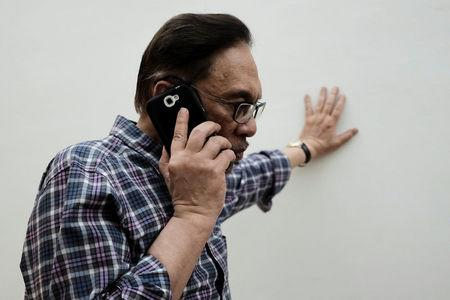 Malaysian politician Anwar Ibrahim takes a phone call during during an interview with Reuters at his house in Kuala Lumpur, Malaysia May 17, 2018. REUTERS/Stringer