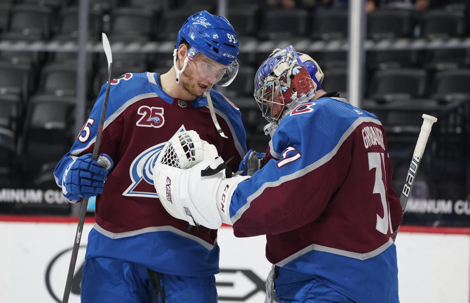 Colorado Avalanche left wing Andre Burakovsky, left, congratulates goaltender Philipp Grubauer after an NHL hockey game against the Arizona Coyotes, Monday, April 12, 2021, in Denver. The Avalanche won 4-2. (AP Photo/David Zalubowski)