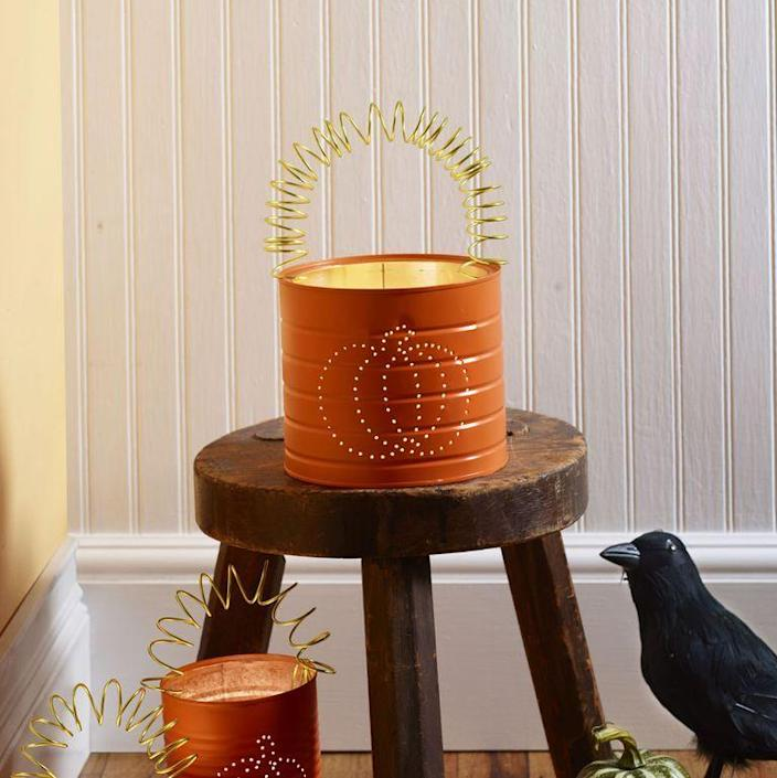 """<p>These embellished pumpkin cans will brighten up your porch or walkway for trick-or-treaters. </p><p><strong>1. </strong>Draw pumpkin design on metal can with permanent marker. Fill can with water and freeze.</p><p><strong>2. </strong>With a nail and a hammer, poke holes every <span>¼-inch </span>to <span>½-inch </span>along the design. Poke a hole on either side at the top for a handle.</p><p><strong>3. </strong>Once water has melted and can is dry, apply orange spray paint; let dry.</p><p><strong>4. </strong>Cut a <span>24-inch</span> piece of wire and coil around the marker. Stretch out and hook into holes on sides.</p><p><strong>What You'll Need: </strong><a href=""""https://www.jamaligarden.com/embossed-aluminum-wire.html"""" rel=""""nofollow noopener"""" target=""""_blank"""" data-ylk=""""slk:12-gauge embossed apple green aluminum wire"""" class=""""link rapid-noclick-resp"""">12-gauge embossed apple green aluminum wire</a> ($7, Jamali Garden)</p>"""