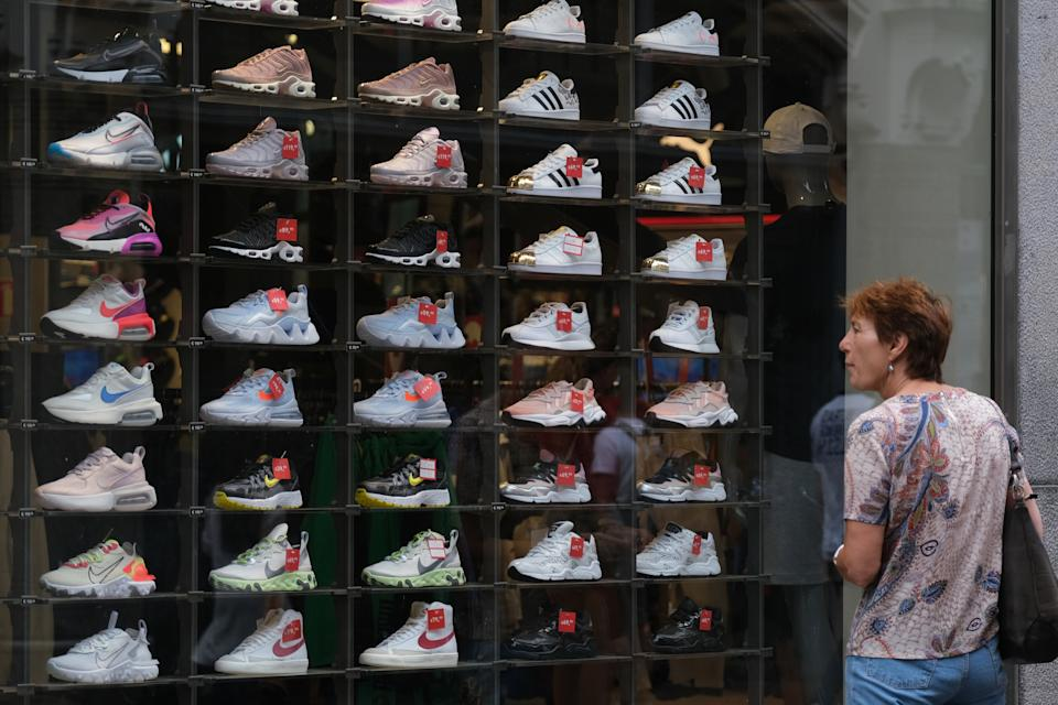 AMSTERDAM NETHERLANDS - JUNE 27: A woman looks at sports sneakers, including brands such as Nike, Adidas, and New Balance, displayed inside a window of Foot Locker at Kalverstraat, a shopping street, on June 27, 2020 in Amsterdam, Netherlands.  (Photo by Yuriko Nakao/Getty Images)