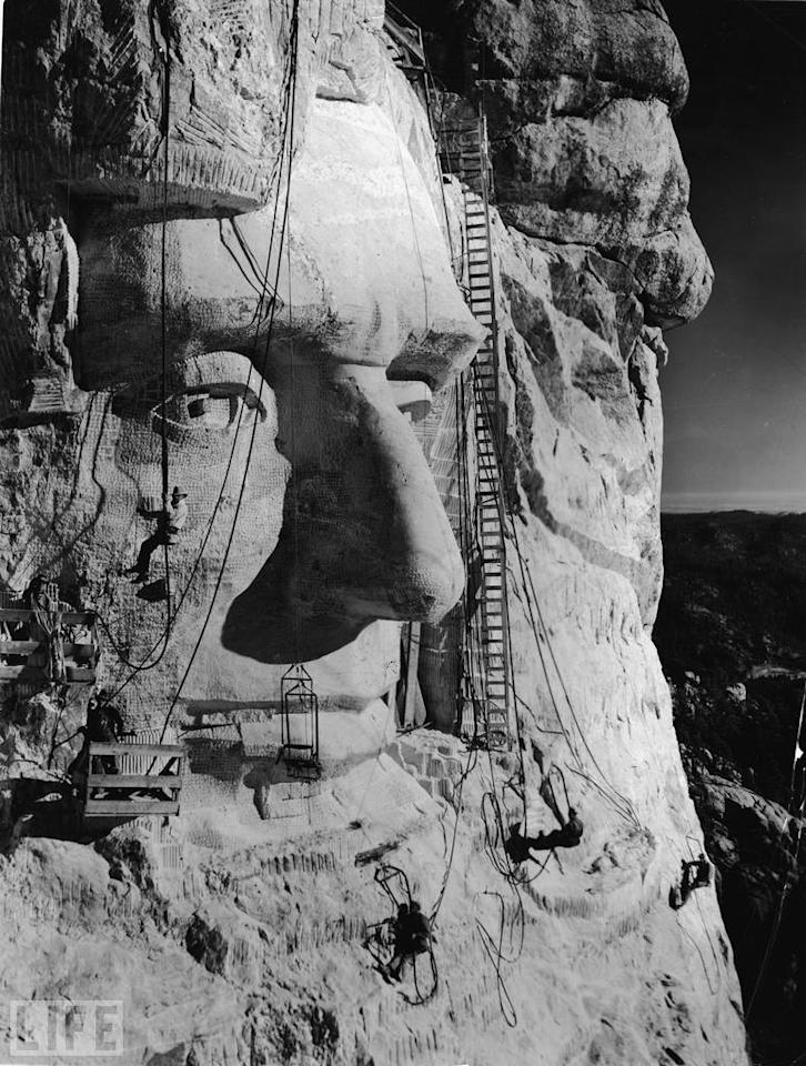 When he began the Mount Rushmore project, sculptor Gutzon Borglum (pictured here hanging below the eye) was an active member of the Ku Klux Klan. He would later deny his relationship with the racist group in an attempt to preserve his reputation. Borglum had been involved in sculpting the Confederate Memorial Carving, a massive bas-relief memorial to Confederate leaders on Stone Mountain in Georgia. October 31 marks the 70th anniversary of Mount Rushmore's completion. Photo: Frederic Lewis/Getty Images